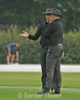 Umpires Jansen and Van Liemt decide that it is not raining hard enough to get off