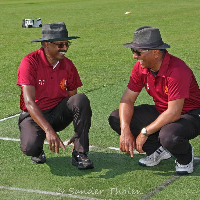 Umpires Das and Muthucumaru testing the wet spot on the pitch